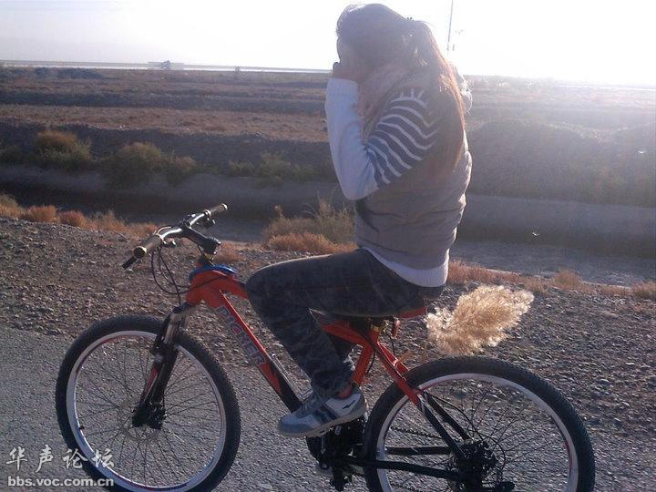 戈壁中骑自行车的志愿者美女图片