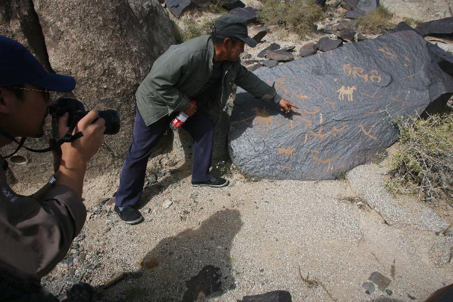 ...右旗曼德拉山,向导向游客讲解一幅反映古代牧民生活的岩画.
